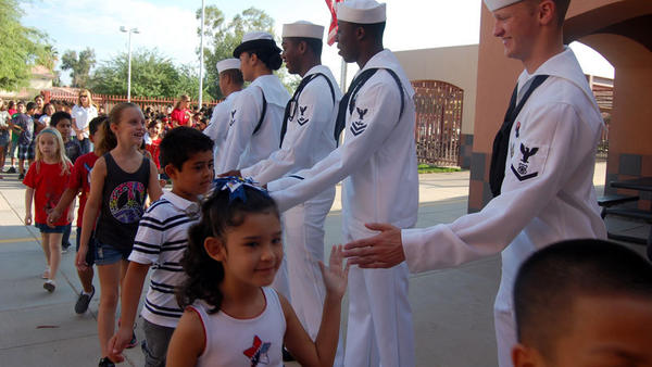 Students give sailors high-fives as they walk back into school after a 9/11 memorial held Tuesday at T.L. Waggoner Elementary School in Imperial.