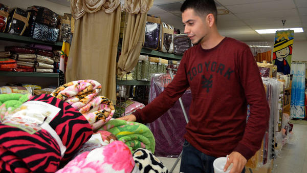 Ali Dahdoul, a Muslim-American Marines recruit, sorts merchandise at his father's store Tuesday in Calexico. He said it was painful to be judged by fellow Americans following the 9/11 attacks.