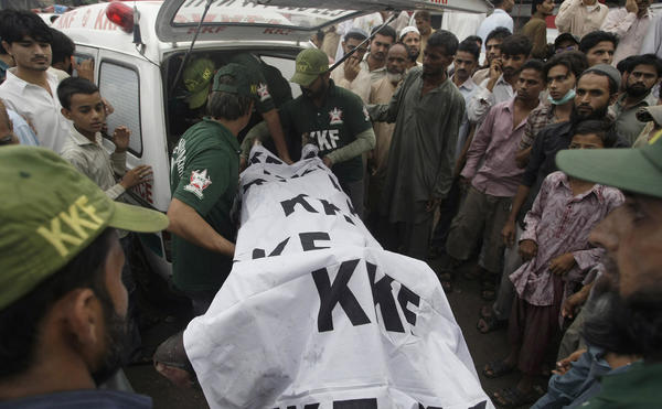 Pakistani rescue workers load a dead body into an ambulance after recovering it from a burnt garment factory in Karachi, Pakistan on Wednesday.