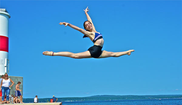 Marie Millard, 14, of Alanson, takes a leap off the Petoskey breakwall this summer. Marie is now studying at the School of American Ballet year-round with her sister Claire, 17.