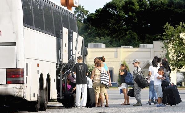 Passengers board a curbside discount bus to New York City in a strip mall parking lot in Hampton on Aug, 17.