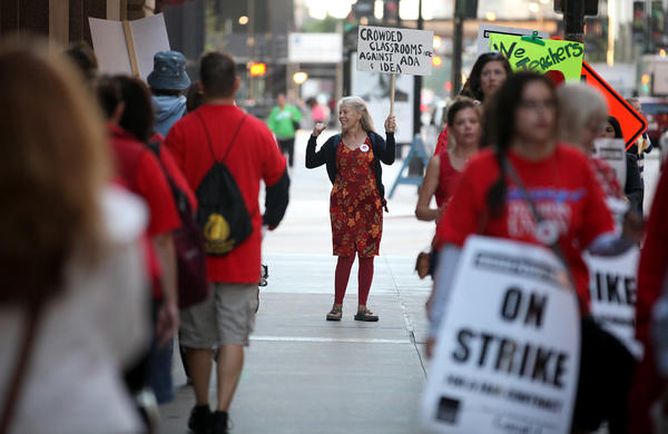 Betsy Mensah, a physical therapist at 19 CPS schools, pickets with Chicago Teachers Union members outside the CPS headquarters in Chicago on Wednesday.