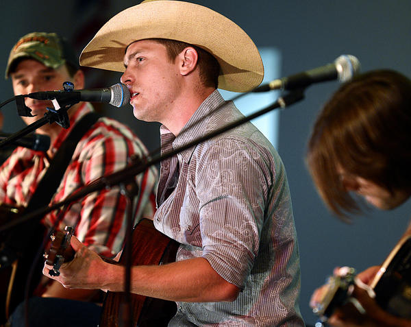 "Country music singer-songwriter Dustin Lynch performs Tuesday night at Harmony United Methodist Church in Falling Waters, W.Va., during a concert to benefit the University of Maryland Medical Center's Living Donor Follow-Up Clinic. Hundreds of fans turned out for the fifth annual benefit concert. Lynch sings the smash, ""Cowboys and Angels."""