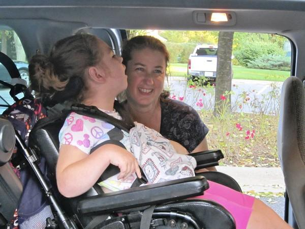 Addie Kurtz, 6, and her mother Cathy check out the interior of a wheelchair accessible van that residents and businesses in Wilmette and Glenview pulled together to buy for the Kurtz family. The van was given to the family during a Sept. 4 ceremony at Cunliff Park in Glenview.
