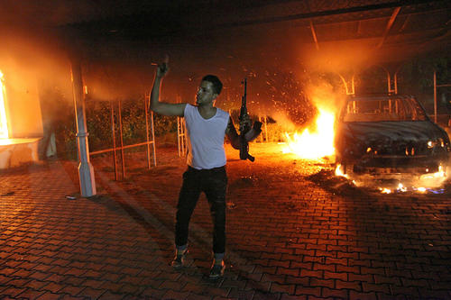 An armed man gestures as buildings and cars are engulfed in flames after being set on fire inside the U.S. consulate compound in Benghazi, Libya.  <b>Warning: The next photo in this gallery contains an image that may be disturbing to some readers.</B>