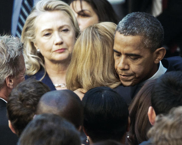 Secretary of State Hillary Clinton looks on as President Obama hugs a State Department employee. Obama came to the State Department in Washington, D.C., to meet with staff after the killing of U.S. Ambassador to Libya Christopher Stevens and three staff members at the U.S. Consulate building in Benghazi, Libya.