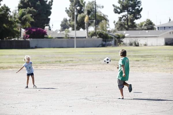 Sadie South, 5, and her brother Blake, 8, play with a soccer ball near a pair of closed school sites off Yorktown Avenue in Huntington Beach on Friday.