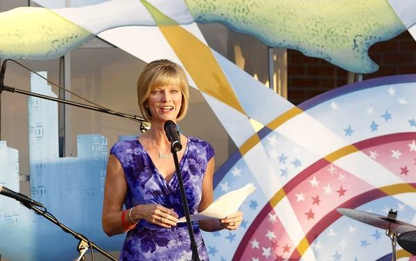 "Sandy Segerstrom Daniels, standing in front of the Festival of Children's ""Believe"" banner, talks to supporters and guests at South Coast Plaza earlier this month."