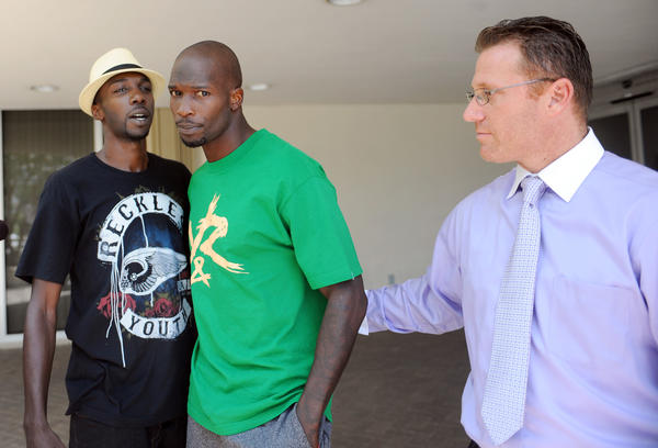 Miami Dolphins wide receiver Chad Johnson, center, is greeted by his brother Chauncey Johnson, left, as his attorney Adam Swickle leads him away from the Broward County jail, Sunday, August 12, 2012, in Fort Lauderdale,