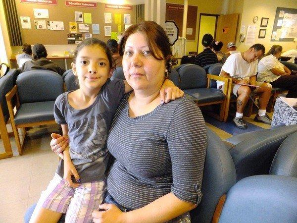 Claudia Pedroza, 39, and her daughter Karla Osorio wait in July at the Jefferson Action Center in Lakewood, Colo. Pedroza and her husband struggle to make ends meet for them and their four children. She was at the center to apply for help with food, toiletries and getting a new frying pan.