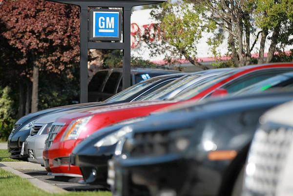 A General Motors logo hangs over cars ready for sale at a Chevrolet dealership in Redwood City, Calif., last year.