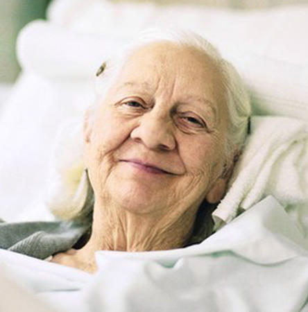 Elderly woman smiling, lying in hospital bed