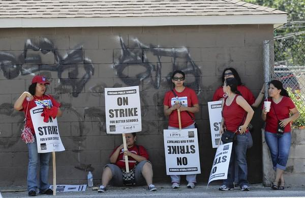 Striking Chicago teachers find shade behind a garage at a rally across from Kelly High School on the South Side on Wednesday.