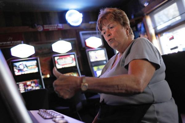 Waitress Mary Callisen wins a hand of video poker at Bringer Inn in Morton Grove, which became the first site in the state to offer legalized video gambling when regulators brought the machines online to test a centralized computer system.