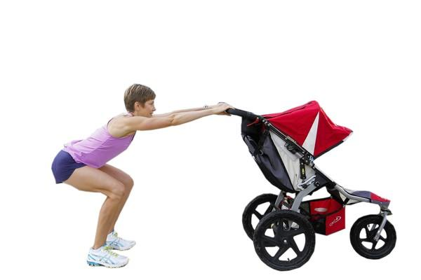 Stroller Strides fitness instructor Jennifer Lungren demonstrates the Squat Starting exercise with a stroller in Alexandria, Virginia. For this exercise, Squat Starting in a standing position with your hands on the stroller handlebars, place your feet hips-width apart with your feet and knees facing forward. Sit down as if you're reaching backwards into a seat, and squeeze your glutes and thighs to bring yourself back into the starting standing position. Push the stroller out as your sit, and pull it back in as you come up.