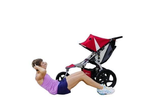 Stroller Strides fitness instructor Jennifer Lungren demonstrates the Peek-a-boo Stroller Crunches exercise with a stroller in Alexandria, Virginia. For this exercise, lie on your back next to your stroller facing your baby with your feet flat on the ground, knees bent at 90-degrees. Put your hands behind your head, keeping your elbows back. Squeeze your belly button to your spine and crunch up. As you come up, peek into your stroller, saying 'Peek-a-boo' to your baby, and lower back down. Exhale as you come up, keeping your elbows back.