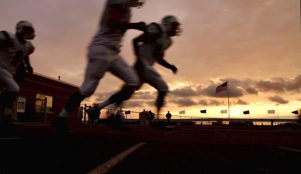 LaSalle-Peru High School football players take the field Friday night in Rochelle, Ill.