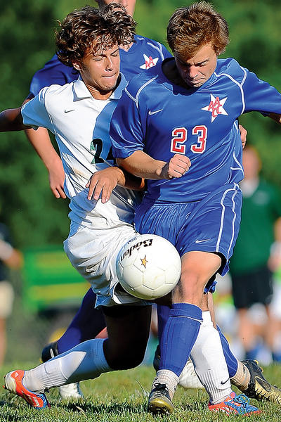 Hagerstown Community College's Jordan Dickins (24) tries to make a path to the goal around the defense of Anne Arundel's Matt Matousek (23) on Wednesday during the Hawks' 3-2 overtime loss.