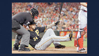 Pittsburgh Pirates' A.J. Burnett, center, falls to the ground after striking out with the bases loaded in the fourth inning of a baseball game against the Cincinnati Reds on Wednesday in Cincinnati. Home plate umpire Manny Gonzalez helps out at left.