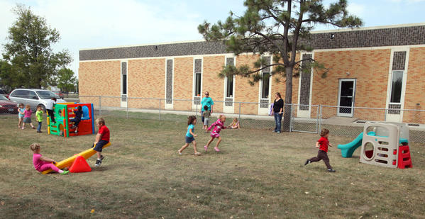 Head Start students run about in the fenced-in outdoor play area Tuesday at the new location in the former K.O. Lee offices. American News Photo by John Davis