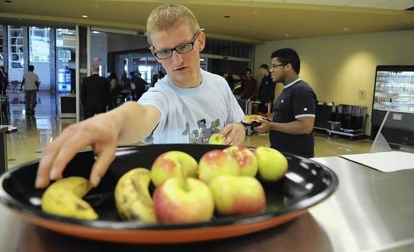 Catasauqua High School senior Chris Creyer picks out some fruit during lunch Wednesday. New federal regulations require students to pick a fruit and vegetable as part of a school lunch. If they don't, it will cost them and the school district more.