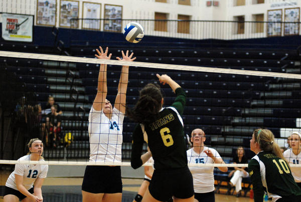 Petoksey junior Jayme Larson (left) goes up for a block as Traverse City West senior Megan Traines spikes the ball Wednesday at the Petoskey High School gym.