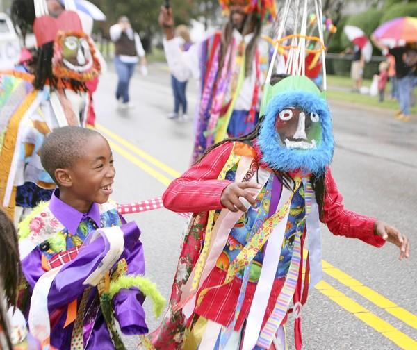 Jelani Francis, 7, left, of Newport News, watches fellow MasKaraider Ayinde Richards dance during the 2011 Denbigh Day parade.