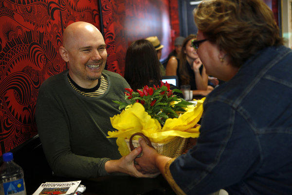 Billy Corgan, of Smashing Pumpkins, receives a good luck pepper plant from Highland Park resident Linda Iovino on the opening day of Madame ZuZu's, a Highland Park tea shop at 528 Roger Williams Ave. that he co-owns with Sharon Mackin-Norberg.