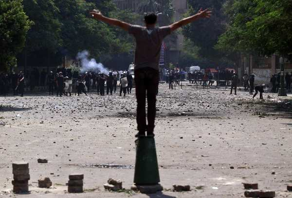 An Egyptian protester stands in front of riot police during the third day of clashes near the U.S. embassy in Cairo. Egypt's Islamist President Mohammed Morsi vowed to protect foreign embassies in the city.