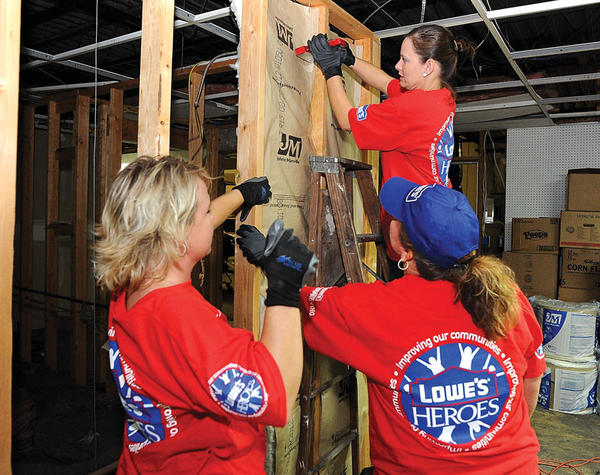 Volunteers from Lowes insulate and hang drywall at Clark County Community Services, part of the Lowes Heroes Project. Pictured here are Donnetta Rice, stapling insulation, while Jenni Huduck, left, and Angelia Brockman hold it in place.