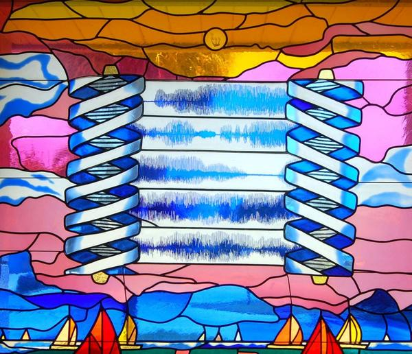 "A tech-looking Torah floats above the ocean in this stained-glass window at Temple Bat Yam in Fort Lauderdale. The spiral-shaped spools are meant to stand for DNA, the genetic code. And instead of text, the scroll shows the soundwave equivalent of the Shema, the basic Jewish creed of monotheism. The  sailboats and water recall the temple's name, which is Hebrew for ""Daughter of the Sea."""