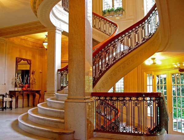 The grand floating, curving, three-story baroque staircase is one of the highlights of the home.