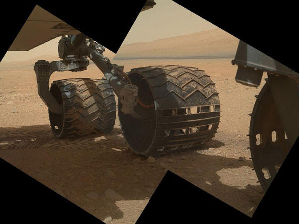 A NASA handout photo shows the three left wheels of NASA's Mars rover Curiosity combined in two images that were taken by the rover's Mars Hand Lens Imager (MAHLI) on September 9, 2012. In the distance is the lower slope of Mount Sharp. REUTERS/NASA/JPL-Caltech/Malin Space Science Systems/Handout (UNITED STATES - Tags: SCIENCE TECHNOLOGY) THIS IMAGE HAS BEEN SUPPLIED BY A THIRD PARTY. IT IS DISTRIBUTED, EXACTLY AS RECEIVED BY REUTERS, AS A SERVICE TO CLIENTS. FOR EDITORIAL USE ONLY. NOT FOR SALE FOR MARKETING OR ADVERTISING CAMPAIGNS