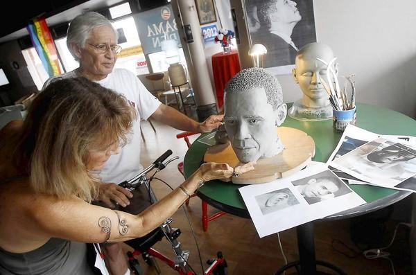 Artists Jessica Destefano, left, and Nick Hernandez smooth out portions of the Obama head sculpture at the Democrat headquarters in Laguna Beach.