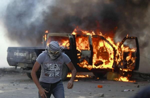 A protester runs from a burning police car near the U.S. Embassy in Cairo.