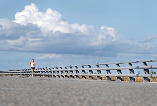 Susan Dickerson takes advantage of the mild fall day by going for a run along the shoreline of Fort Monroe on Thursday, September 13, 2012.