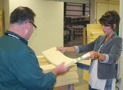 U.S. Rep. Kristi Noem, R-S.D., examines a piece of foam-like material used in the construction of wind blades at the Molded Fiber Glass plant in Aberdeen during a visit in August. Richard Frankhauser, materials manager, is handing her the product.