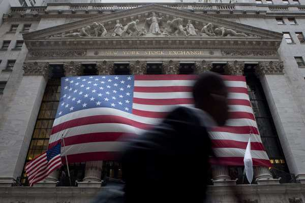 A pedestrian walks past as workers hang a giant American Flag on the exterior of the New York Stock Exchange.