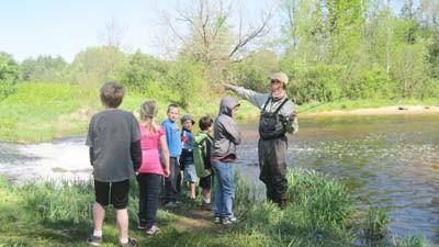 Angler Brian Kozminski of Boyne City talks to a group of children about fly fishing at the Philip J. Braun Preserve near Pellston.