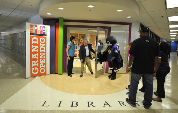 The Baltimore Raven's bird, Poe holds the door open for Dave Gimbel  with Signs by Tomorrow. The Weinberg Foundation will reveal one of the first of its $1 million libraries it has committed to building in Baltimore city in four years.