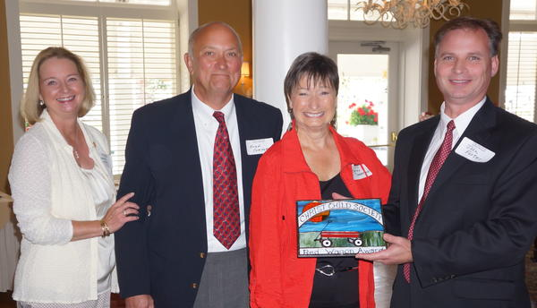 Debbie Dicken (left), president of the Christ Child Society of Northern Michigan and Kathy Thompson (center) present the 2012 Red Wagon Award to Brad Comport (left), president of Birchwood Golf and Country Club board of trustees, and John Foster, general manager of Birchwood Golf and Country Club.