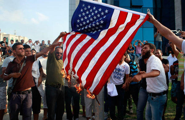 Tunisian protesters burn the U.S. flag during a demonstration outside the U.S. embassy in Tunis.