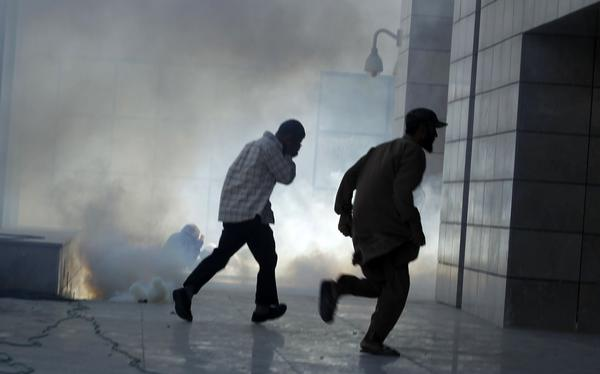 Protesters run for cover during a demonstration in front of the U.S. Embassy in Tunis September 14, 2012. At least five protesters were wounded when Tunisian police opened fire on Friday to quell an assault on the U.S. embassy compound.