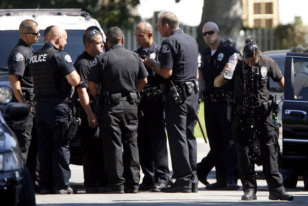 A Glendale Police officer cools down by pouring a bottle of water on her head as other members of the dept. strategize while they look for a burglary suspect on the 1800 block of Cleveland Rd. at Crestview Ave. in Glendale on Thursday, Sept. 13, 2012.