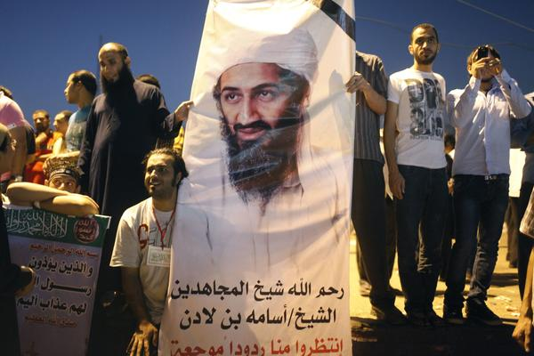 "Demonstrators carry a poster of Osama Bin Laden during a protest condemning a U.S. produced movie insulting Islam's Prophet Mohammad in Tahrir Square September 14, 2012. The poster reads: ""May God have mercy on the soul of Sheikh Osama Bin Laden. Wait for more hurtful reactions from us."""