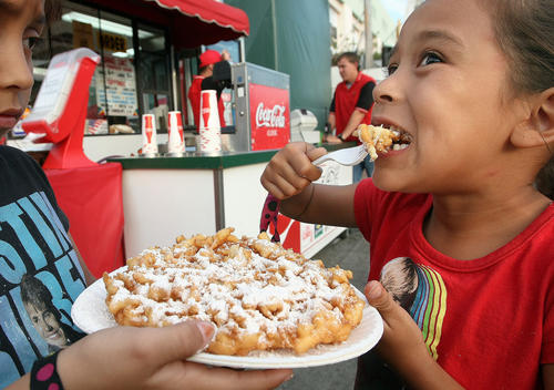 Veysa Del Real, 7, tries out the funnel cake, which is not in any recommended food group, last week at the L.A. County Fair.