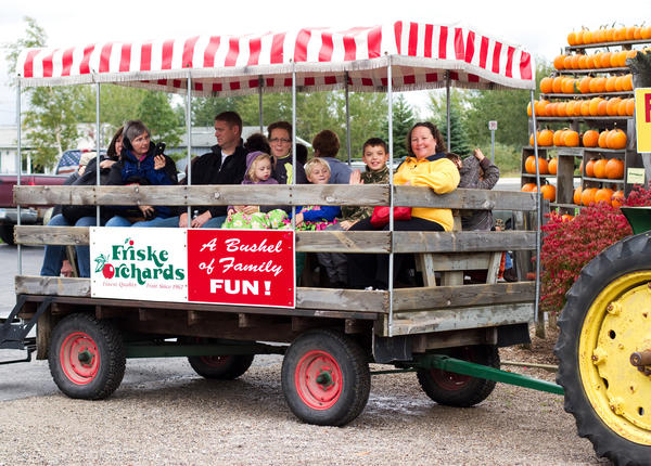 Visitors go on a tractor-drawn wagon ride through an apple orchard at Friske's Farm Market's Harvest Festival last year.