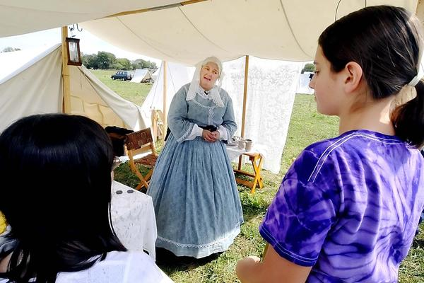 Maurine Beechler of Buffalo, Ny., talks with Smithsburg Middle School students Jade Lee, left, and Talia Seidman about women's fashion during the Civil War era.
