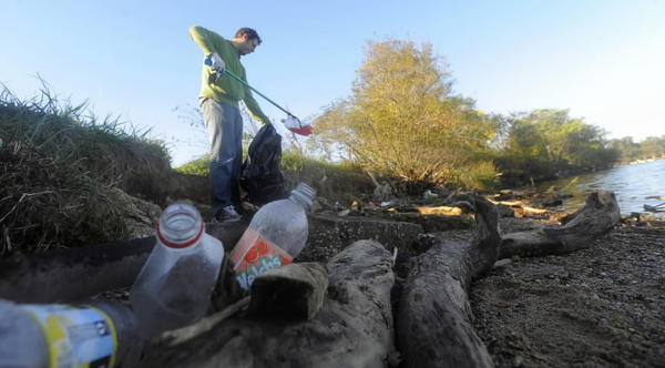 Volunteer picks up trash along Middle Branch in Baltimore. Ten cleanups have been planned in the area.