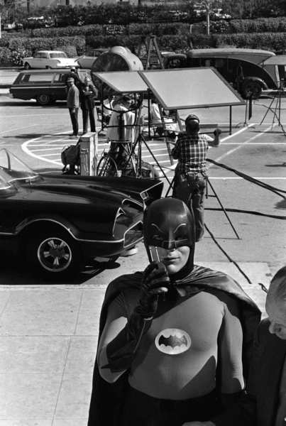 "Holy Caped Crusader! Adam West, star of the ABC-TV series ""Batman,"" stands beside the Batmobile while using his ""Bat Radio"" on the set in Hollywood on March 18, 1966."